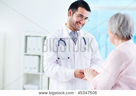 Sicher Arzt betrachtet seine leitenden Patientin beim sprechen mit ihr
