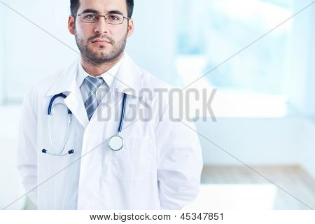 Portrait of serious doctor with stethoscope looking at camera