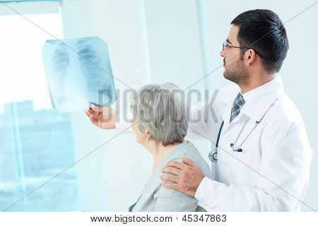 Confident doctor showing x-ray to his senior patient in hospital