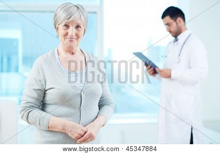 Senior patient looking at camera with doctor working on background