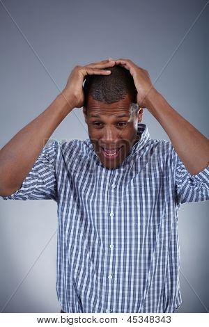 Image of young African man holding his head in astonishment