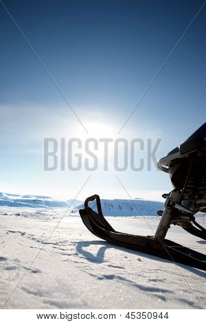 Snowmobile against a deep blue sky