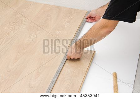 Carpenter Worker Installing Laminate Board During Flooring Work