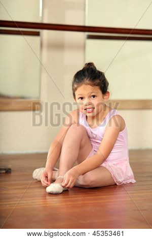 Cute little girl adjusting her ballet shoes