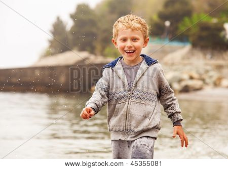 Cute Smiling Little Boy Run In Water Drops