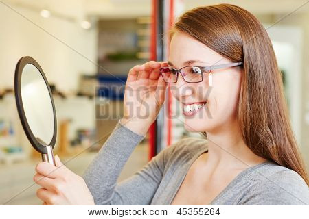Young woman checking her new glasses in a mirror at optician retail store