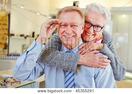 Happy senior couple with new glasses at optician retail store