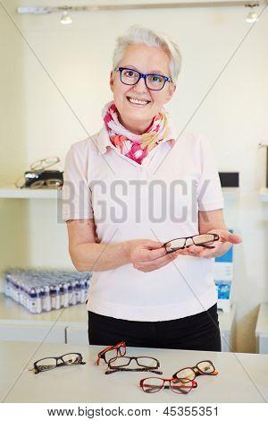 Senior optician giving consultation for new glasses