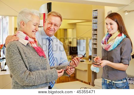 Happy senior couple buying new glasses at optician store