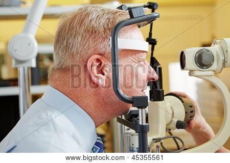 Senior man at eye measurement at ophthalmologist with slit lamp