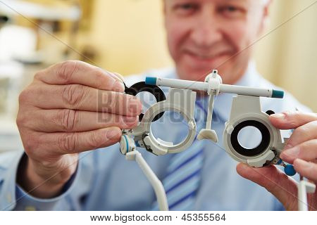 Optician with trial frame to determine prescription values of glasses