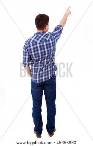Young casual man pointing towards copyspace, isolated on a white background