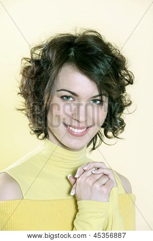 portrait in studio of a young caucasian  woman toothy smiling on yellow background  a yellow sweater