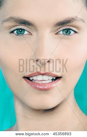 studio shot beauty portrait of a beautiful green eyes caucasian young woman on a blue background