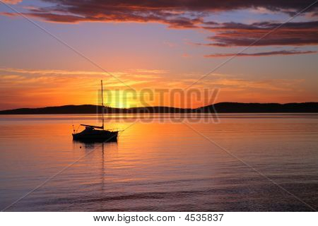 Sailing Boat Moored On Calm Water At Sunrise