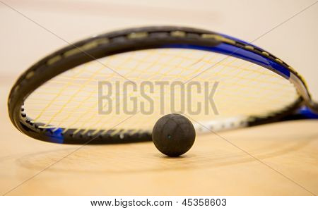 Squash racket with a ball at the court