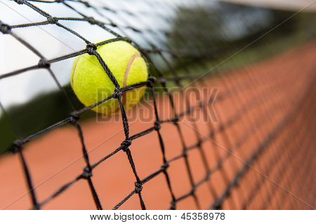 Tennis ball bouncing on the net at a clay court