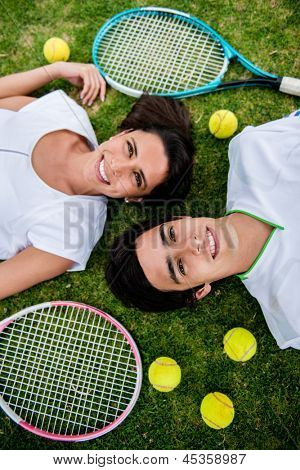 Couple of tennis players lying in the floor with rackets and balls