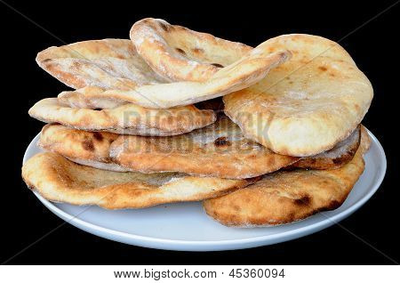 Indian Naan bread stacked on plate.