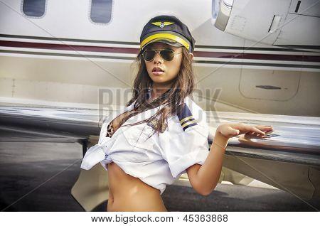 Beautiful woman posing glamor style beside aircraft plane