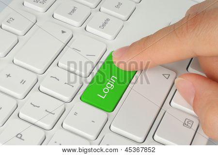 Hand pushing green login keyboard button