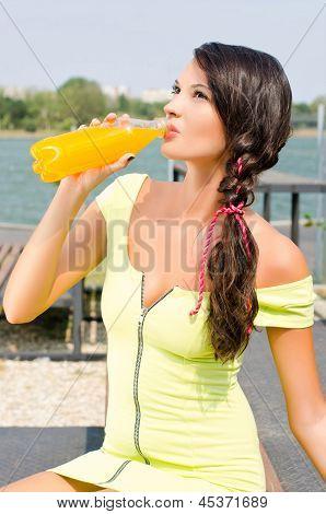 Beautiful brunette girl drinking orange juice from a plastic bottle.