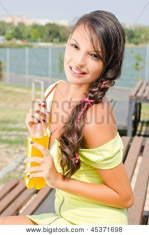 Beautiful brunette girl holding a plastic bottle with orange juice.