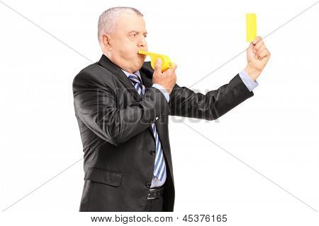 A mature businessman blowing a whistle and showing a yellow card, isolated on white background