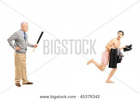Full length portrait of a middle aged man with baseball bat shouting at a young naked man running away, isolated on white background