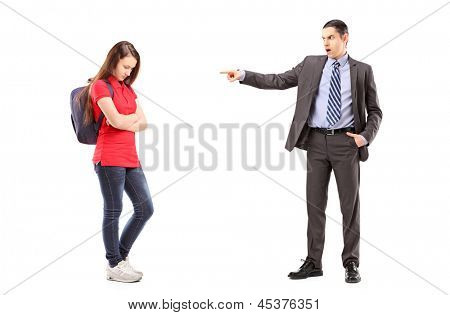 Full length portrait of an angry father shouting and pointing with his finger at his daughter, isolated on white background