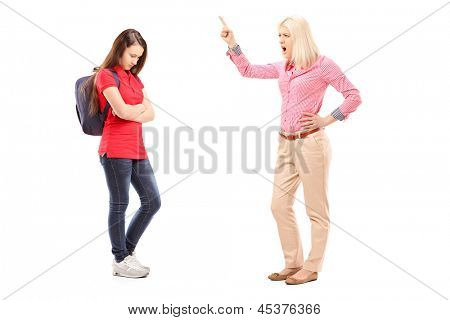 Full length portrait of an angry mother shouting at her daughter isolated on white background