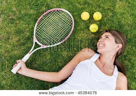 Tennis player lying on the floor with racket and ball