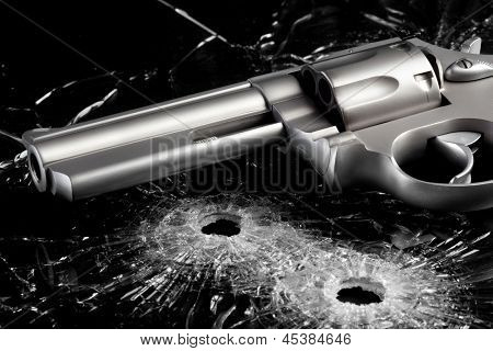 Gun with two bullet holes in glass over black - modern revolver close up
