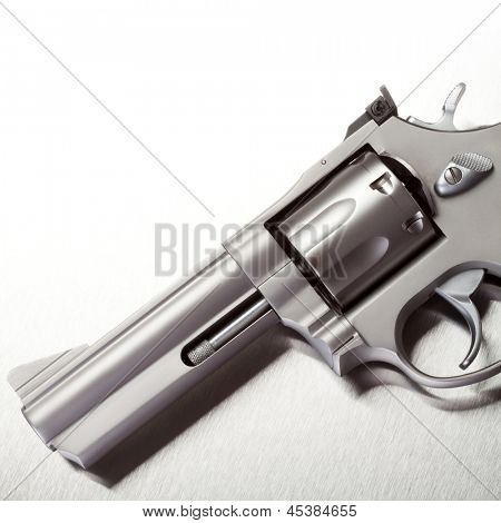 Handgun on brushed metal background, white above