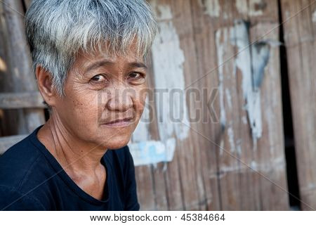 Asian senior from an impoverished area, outside her home in the Philippines