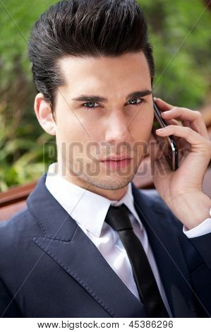 Young Businessman Talking On Phone Outside The Office