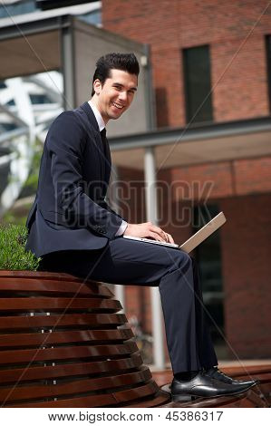 Happy Businessman Working On Laptop Outside The Office