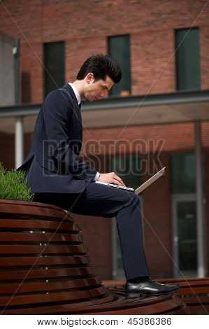 Young Businessman Working On Laptop Outside The Office