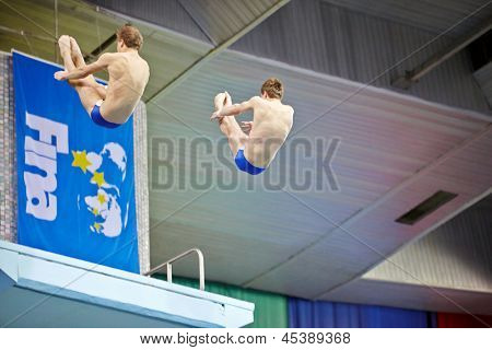 MOSCOW - APR 13: Athletes perform exercise during competitions on syncronized springboard diving in Pool of SC Olympic on day of third phase of World Series of FINA Diving, April 13 2012 Moscow Russia