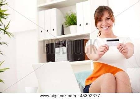 young smiling woman in dress holding card sittinng on sofa at home
