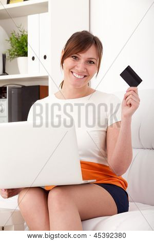 Closeup portrait of an attractive young woman with a laptop and card sitting on sofa at home