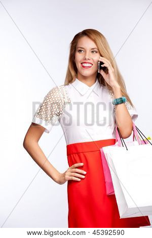 Happy beautiful woman with shopping  gift bags talking on cellular mobile phone, cheerful smiling on a white background