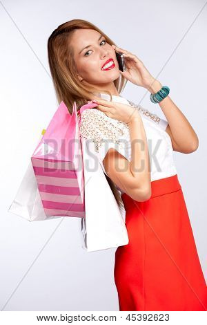 Happy beautiful woman with shopping  gift bags talking on cellular mobile phone, cheerful smiling on a grey background