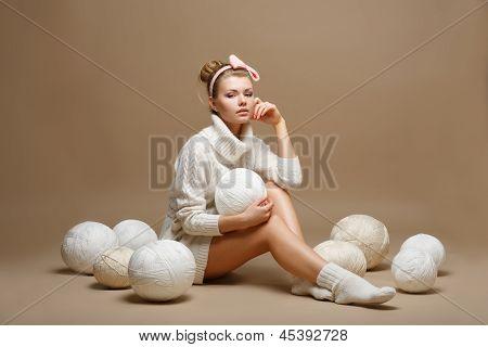 Tareas domésticas. Mujer joven en Tricot blanco con bolas de lana. Costurera