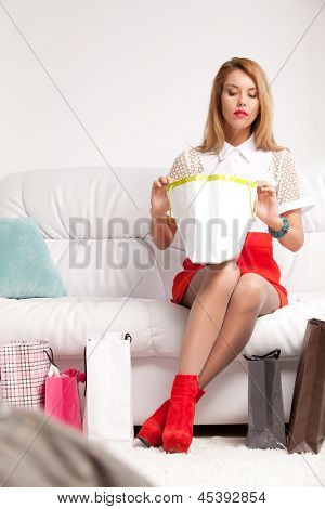 young woman looking into shopping bag sitting on sofa at home