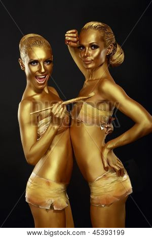 Fancy Dress Party. Couple Of Women With Golden Metallic Painted Skin. Creativity