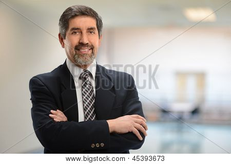 Hispanic businessman with arms crossed inside office building