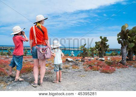 Madre y dos hijos de senderismo en el terreno escénico en Galápagos