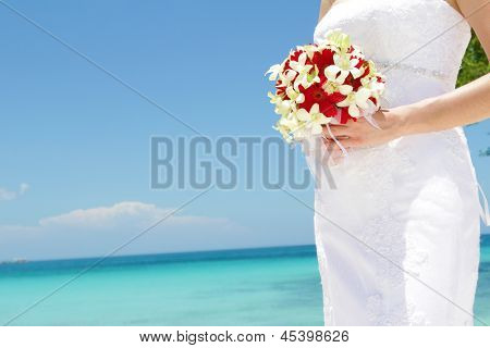 bride holding bridal bouquet on natural sea background, wedding on tropical beach
