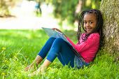 stock photo of braids  - Outdoor portrait of a cute young black little girl reading a book  - JPG